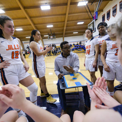 Northland College women's basketball coach Daryl Tucker in the middle of a huddle.