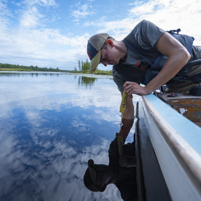 Northland student Andy Kasun takes a water sample.