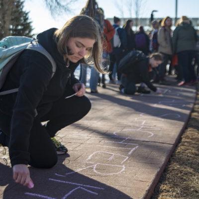 Northland College student writes message on sidewalk in chalk.