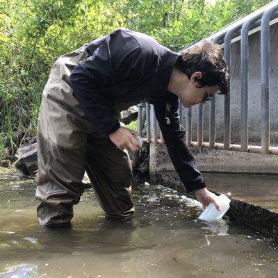 Northland College student collects water sample.