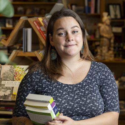 Northland College alum Halee Kirkwood holds books inside bookstore.