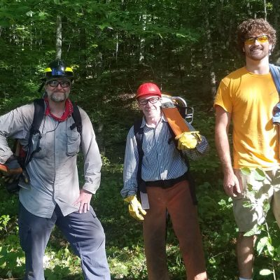 Northland College professors and student working on trails.