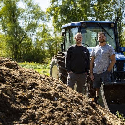 Big Lake Organics owners Jamie Tucker and Todd Rothe stand near compost pile.